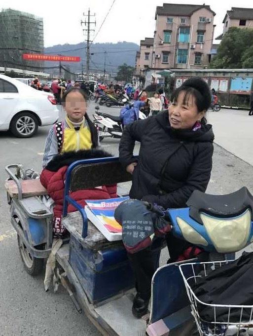 曾四清骑三轮车接小女儿放学。